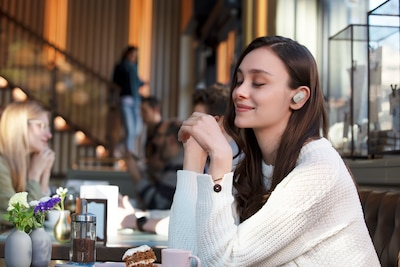 Lifestyle image of woman in cafe enjoying WF-1000XM3 headphones