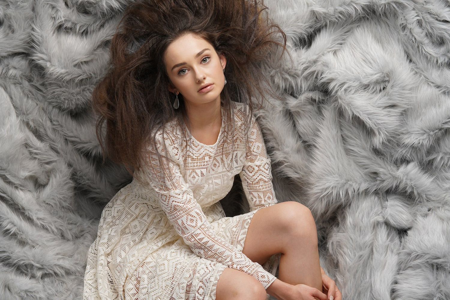 mid-shot-model-in-white-dress-against-fur-background-alpha-7RIV