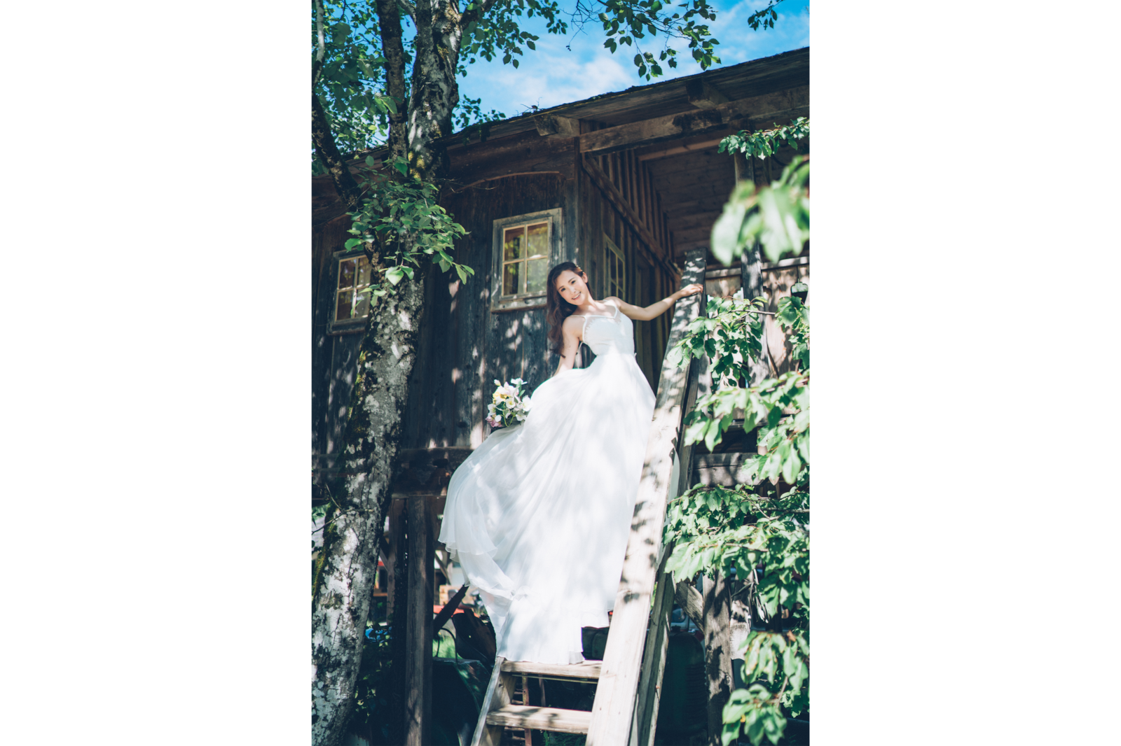 bride in white gown standing on steps of hut