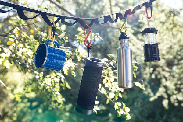 SRS-XB23 hanging from carry strap outdoors by trees.