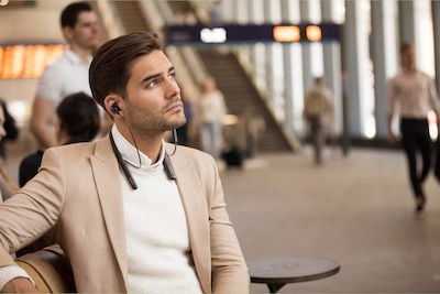 Lifestyle image of man waiting at station wearing WI-1000XM2 headphones