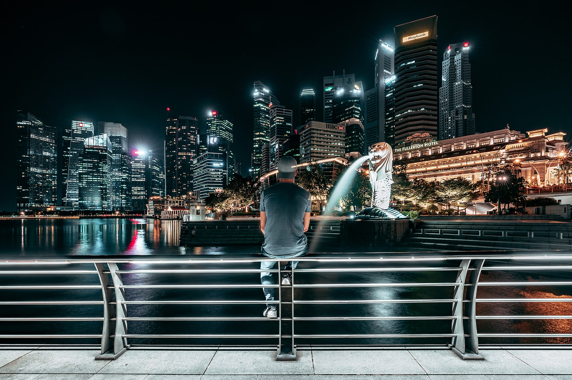 Man sitting on railings by Singapore river facing Merlion at night