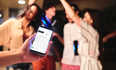Person holding smartphone showing Sony | Music Center app