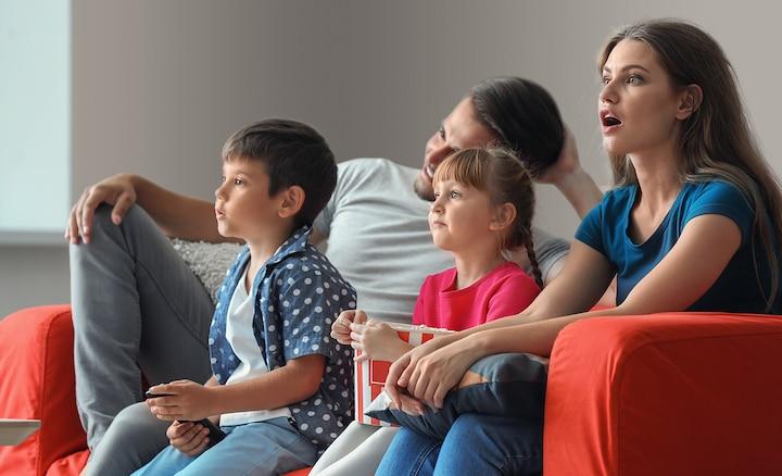 Keluarga menonton TV dari sofa