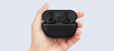 Close-up of hand holding open charging case with WF-SP800N headphones inside.